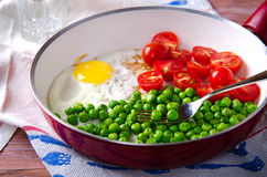 Breakfast with fried egg, green peas and cherry tomatoes Royalty Free Stock Image