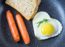 Breakfast fried egg in heart-shaped, grilled sausages, bread, fresh dill, top view, in the pan, dark background Stock Image