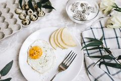 Breakfast of fried egg and pear on a white plate with a fork. In a glass bowl, yogurt and a dragon fruit, next to a tray of quail. Eggs, tablecloth and flowers Stock Images