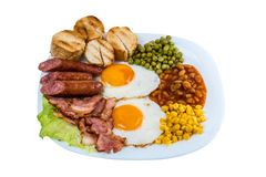 breakfast fried egg peas, corn grains, beans fried sausages and fried bacon on a white plate royalty free stock photo