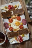 Breakfast with fried egg, rye bread, pomegranate, carob paste, cheeses, olives, dry salami, tomatoes and tea royalty free stock image