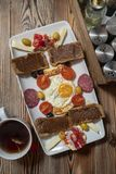 Breakfast with fried egg, rye bread, pomegranate, carob paste, cheeses, olives, dry salami, tomatoes and tea royalty free stock photos