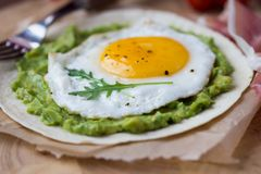 Breakfast with fried egg and sauce of avocado on grilled flour Royalty Free Stock Photo