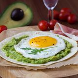 Breakfast with fried egg and sauce of avocado on grilled flour Stock Photo