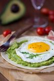 Breakfast with fried egg and sauce of avocado on grilled flour Stock Photos