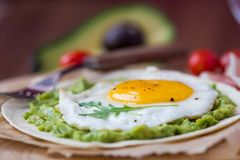 Breakfast with fried egg and sauce of avocado on grilled flour t Stock Photos