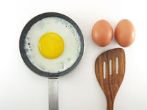 Fried egg in small metal teflon pan with silver steel handle, two raw eggs and brown wooden spatula isolated on white background. Preparation cooking breakfast stock photos