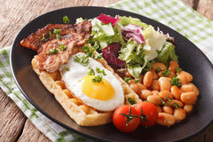 Breakfast with fried egg, waffles, bacon, mix lettuce and beans Royalty Free Stock Photos