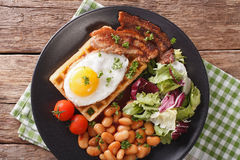 Breakfast with fried egg, waffles, bacon, mix lettuce and beans Royalty Free Stock Images