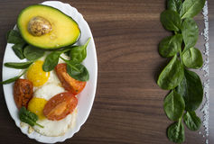 Breakfast. Fried eggs with avocado, spinach and tomatoes Stock Photo