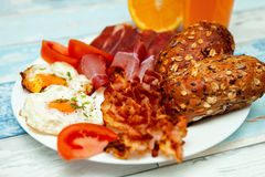 Breakfast with fried eggs, bacon and buns for Chrono diet, Chron. Breakfast with fried eggs, bacon and buns and a plate for Chrono diet, Chrono diet concept Royalty Free Stock Photography