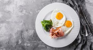 Breakfast, fried eggs, bacon, prosciutto, fresh salad on plate on grey table surface. Healthy food, top view, flat lay. Breakfast, fried eggs, bacon, prosciutto royalty free stock images