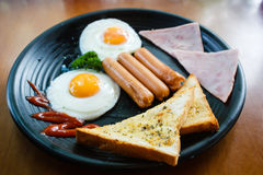 Breakfast with fried eggs, bacon and sausages. Stock Photos