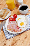 Breakfast with fried eggs and bacon. Toast, orange juice and coffee on a white wooden table, portrait mode Stock Photography