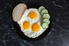 Breakfast. Fried eggs with bread and cucumbers.  stock photography