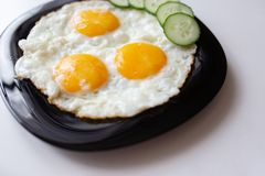 Breakfast. Fried eggs with bread and cucumbers.  royalty free stock photo