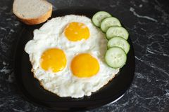 Breakfast. Fried eggs with bread and cucumbers.  royalty free stock image