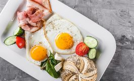 Breakfast, fried eggs, bun, sausage, bacon, prosciutto, fresh salad on plate on grey table surface. Healthy food, top view, flat. Lay stock images