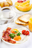 Breakfast. With fried eggs, coffee, orange juice, croissant, toasts  and fruits Stock Images