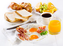 Breakfast. With fried eggs, croissants, juice, coffee and fruits Royalty Free Stock Photos