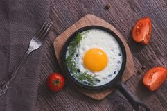 Breakfast of fried eggs in a frying pan with tomatoes and dill. Fried eggs on a wooden table top view.