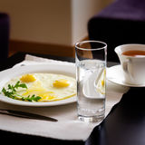 Breakfast with fried eggs. A glass of water, fried eggs and a cap of tee on the table Stock Photos