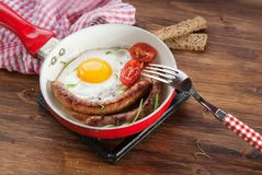 Breakfast with Fried eggs sausages. Breakfast with fried eggs, sausages and tomatoes royalty free stock photography