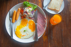 Breakfast with fried eggs, toasts, juice and salad Royalty Free Stock Photo