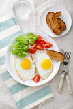 Breakfast - Fried Eggs, tomato, lettuce, bread and water glass Stock Photos