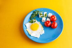 Breakfast. Fried eggs with turkish cheese peynir and whole tomatoes on a blue plate. stock image