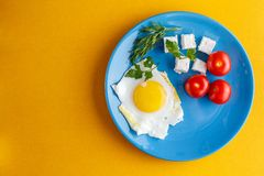 Breakfast. Fried eggs with turkish cheese peynir and whole tomatoes on a blue plate. stock images