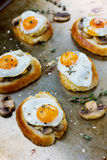 Breakfast with fried quail eggs, mushrooms and toast. On a rustic pan Royalty Free Stock Photos