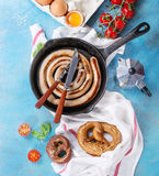Breakfast with fried sausage. Ingredients for breakfast with fried sausage in cast-iron pan, broken egg, tomatoes, pretzels, basil and coffee pot on white Royalty Free Stock Photos