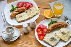 Breakfast with fried sausages, cheese toasts and coffee Royalty Free Stock Image