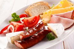 Breakfast - fried sausages, yellow cheese and vegetables. O wooden table Stock Photo