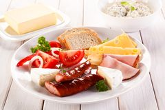Breakfast - fried sausages, yellow cheese and vegetables. O wooden table Royalty Free Stock Photo