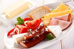 Breakfast - fried sausages, yellow cheese and vegetables. O wooden table Stock Images