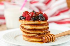 Breakfast. Fritters   with honey and berries - raspberries and blueberries. On a white plate.  Homemade pancakes.  Selective focus Stock Images