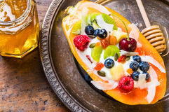 Breakfast fruit bowl with fruits, berries and nuts. Papaya breakfast bowl with yogurt fruits, berries, nuts Stock Photos