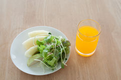 Breakfast. Fruit salad for breakfast in white plate and orange juice on table Royalty Free Stock Photos