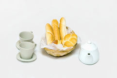 Breakfast with a full bread basket cups and teapots on a white Royalty Free Stock Photography