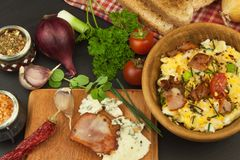 Breakfast full of protein. Scrambled eggs and bacon. A hearty meal for athletes. Homemade recipe for eggs. Royalty Free Stock Photo