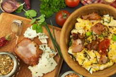 Breakfast full of protein. Scrambled eggs and bacon. A hearty meal for athletes. Homemade recipe for eggs. Royalty Free Stock Images
