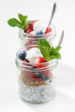 Breakfast in a glass jar, chia with berries and oat flakes o. N white wooden table, vertical, top view Royalty Free Stock Photo