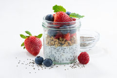 Breakfast in a glass jar, chia with berries and oat flakes. On white table, closeup Royalty Free Stock Photos
