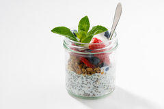 Breakfast in a glass jar, chia with berries and oat flakes. On white wooden table, horizontal, closeup Royalty Free Stock Images