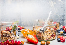 Breakfast in glass jars with muesli, berries, nuts and seeds on light rustic background. Royalty Free Stock Images