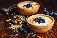 Breakfast with Granola, Banana and Blueberry. Healthy Breakfast with Granola, Banana, Blueberry and Greek Yoghurt. Scattered Ingredients on Wooden Table stock photos
