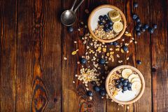 Breakfast with Granola, Banana and Blueberry. Healthy Breakfast with Granola, Banana, Blueberry and Greek Yoghurt. Scattered Ingredients on Wooden Table. View royalty free stock photos