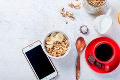 Breakfast granola, a cup of coffee and phone Stock Image